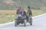 Tibetans driving a tractor on a highway