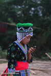 Hmong girl in traditional apparel texting on a mobile phone