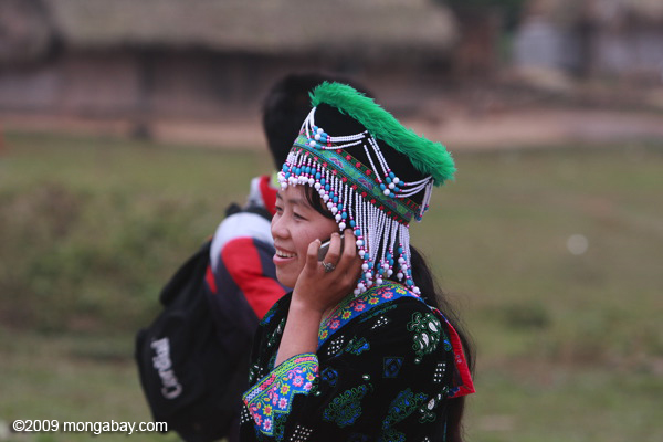 Hmong girl in traditional garb talking on a mobile phone