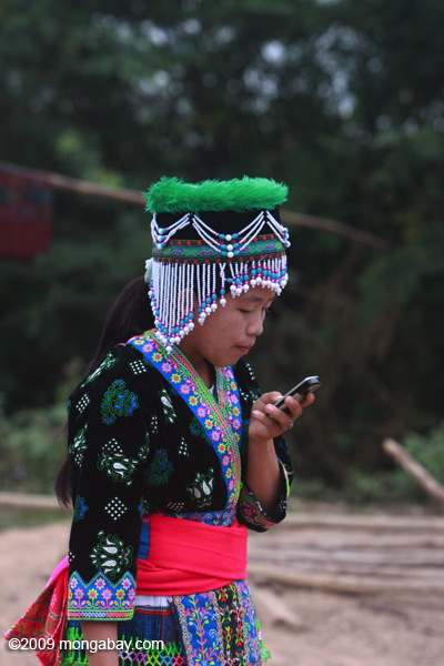 Hmong girl in traditional clothes texting on a mobile phone