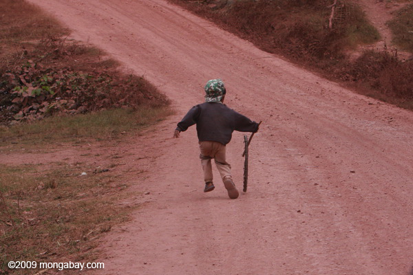 Boy pushing a bicycle tire down a road with a stick