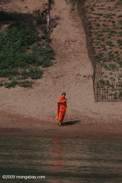 Monk standing on the bank of the Nam Ou river while holding a cell phone